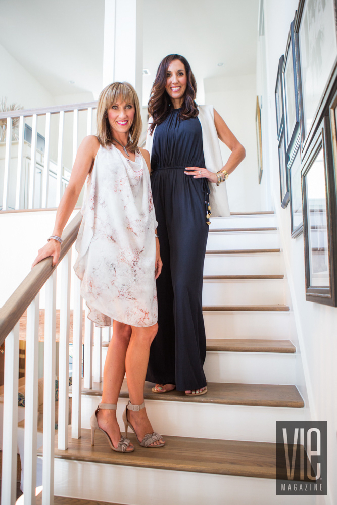 Two women modeling white dress and black romper on stairs