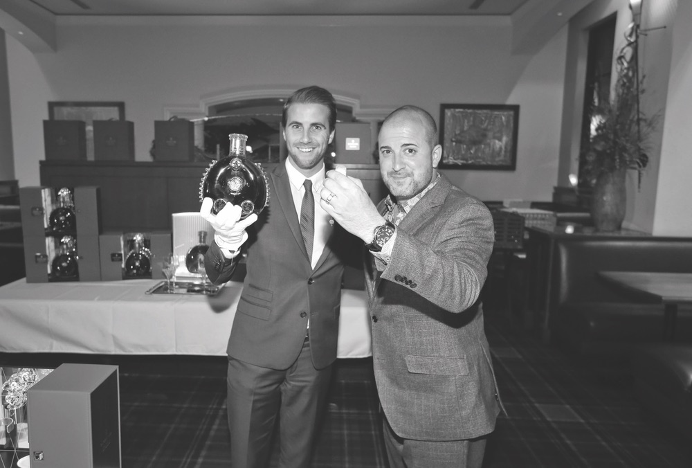 Two men holding up Louis XIII decanter Capt Andersons Celebration The Sophisticate Issue 2016