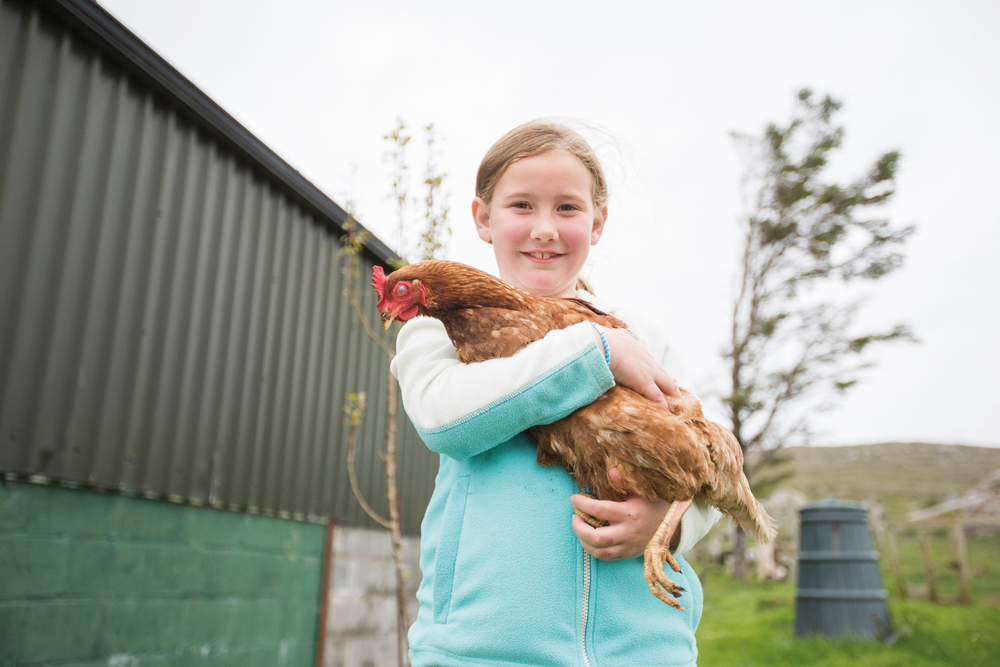 Maria Gorham holding a chicken at Glenbricken Farm The Sophisticate Issue Connemara Life