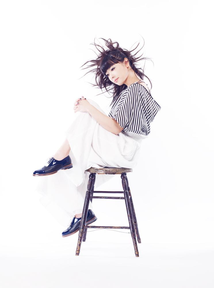 Hiromi Uehara jazz pianist poses on a chair. Photo by Muga Miyahara
