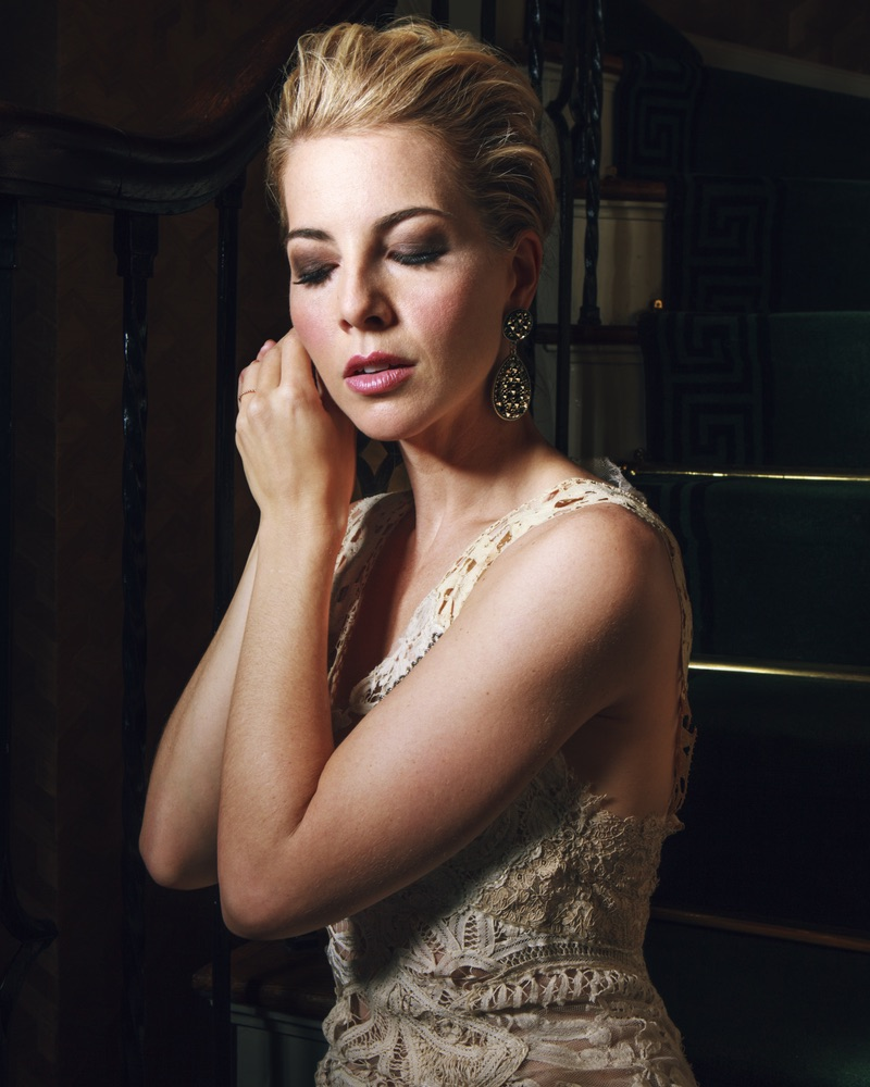 Morgan James putting on her earrings in a stunning Mimi Prober gown The Sophisticate Issue 2016