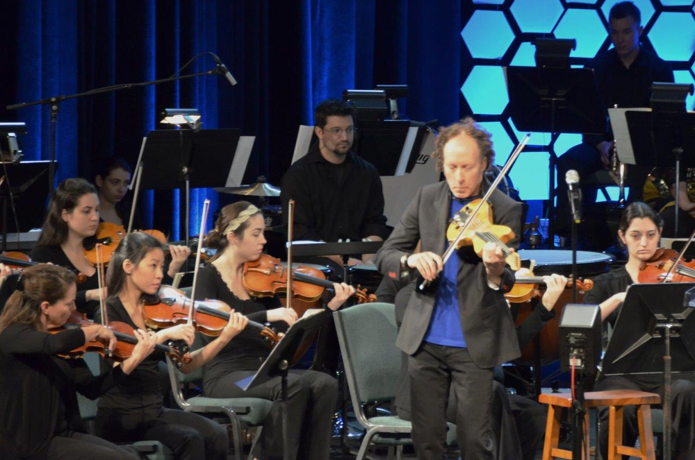 Man leading on violin with youth orchestra