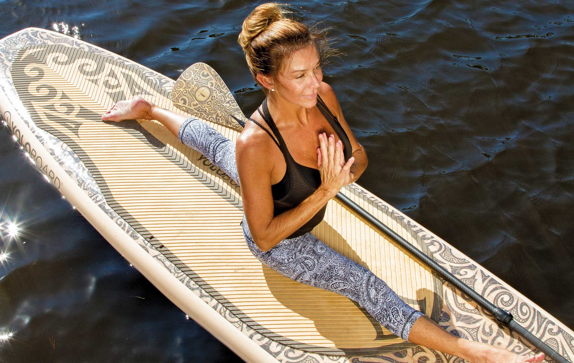 Woman doing paddleboard yoga in Lululemon workout clothing. Photo by Dawn Chapman Whitty.