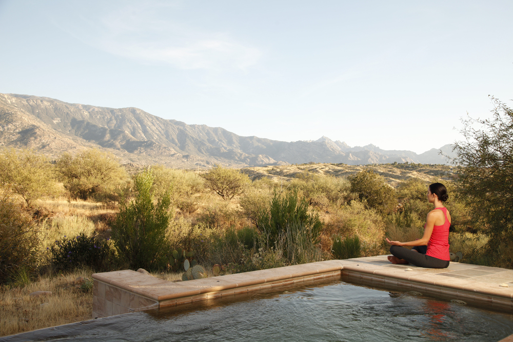 Woman meditating poolside at Miraval Resort in Tuscon, Arizona