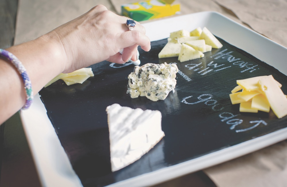 labeling cheese with chalk on cheese platter