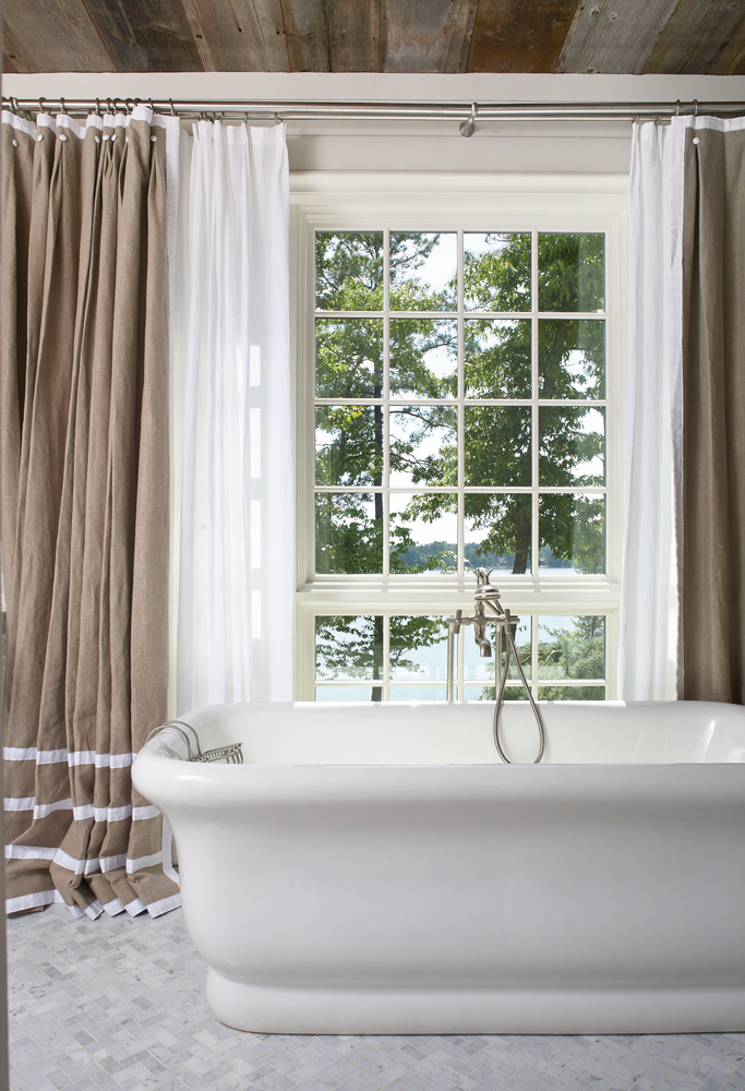 Gorgeous bathtub in front of large windows for natural lighting Lake Martin home