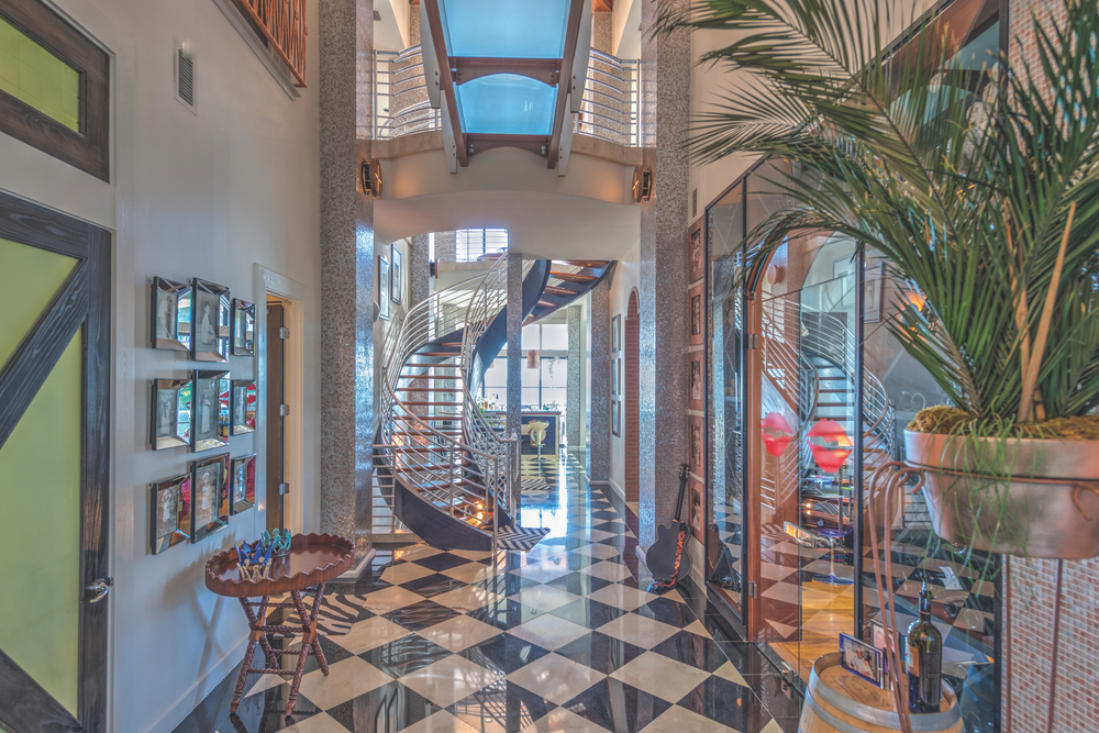 Dr. Bill and Pam Burden home preview. This amazing winding staircase of hardwood treads, stainless steel balustrades, and laminated wood carriage is a spectacular centerpiece to this light and airy two-story gallery.