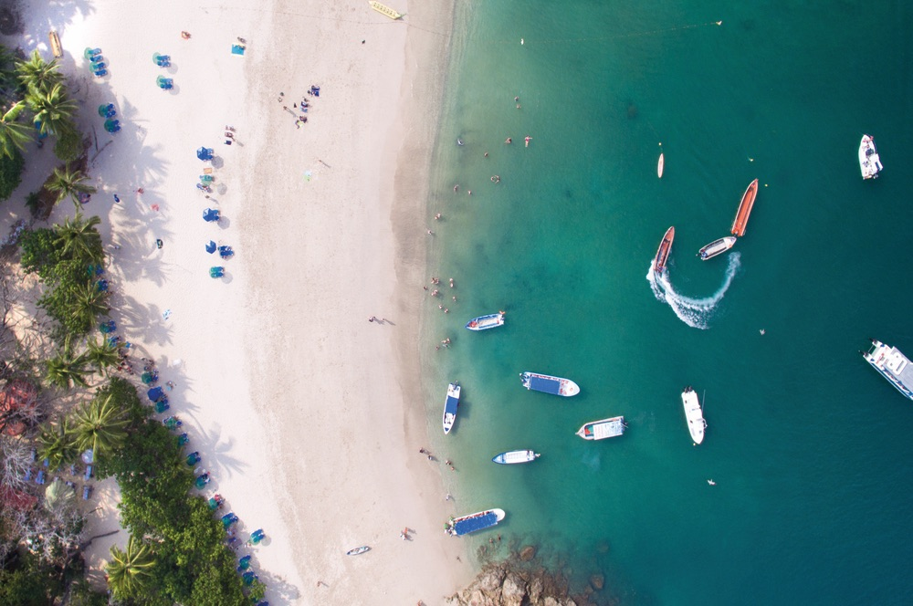 People relaxing on the beach and boats floating in the water represent a typical day on the island of Tortuga, Costa Rica. Chandler Williams, Modus Photography.