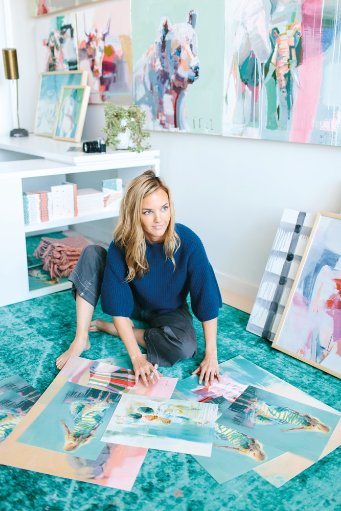 Teil Duncan sitting surrounded by her paintings, photo by Gray Benko