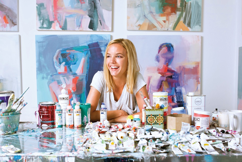 Teil Duncan sitting with her paints and tools, photo by Minette Hand