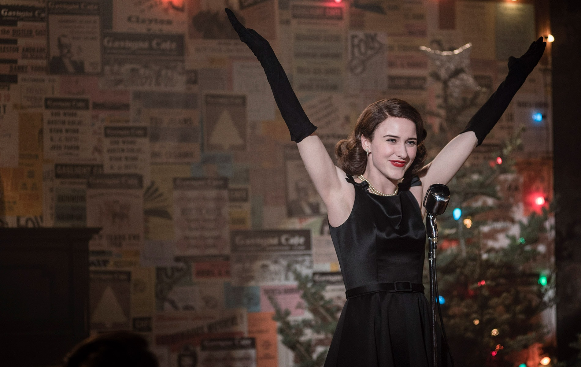 Rachel Brosnahan acting in Season 1 of The Marvelous Mrs. Maisel on stage with her arms thrown in the arm in excitement.