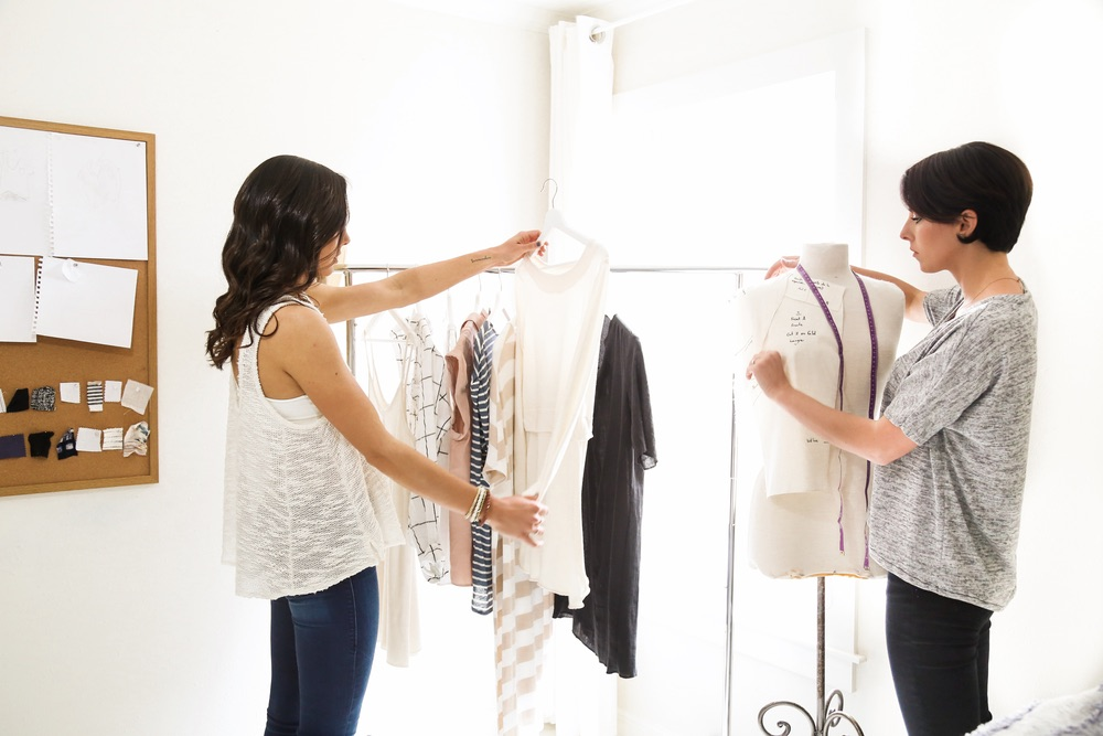 Sisters Katie Steelman and Abbie Boatwright, founders and owners of OKO Lifestyle reviewing garments