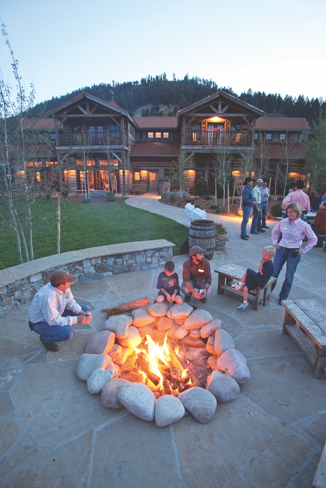 People gather around stone fire pit at The Ranch at Rock Creek