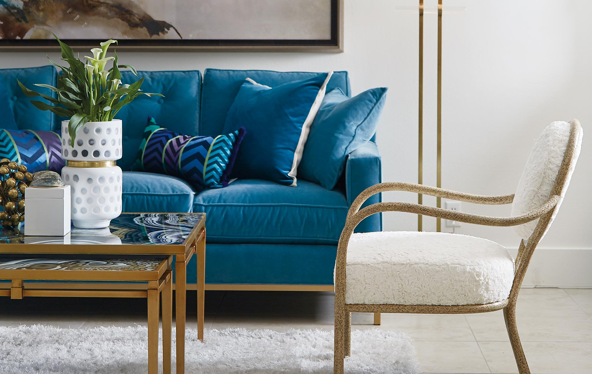Lovelace Showroom with a gorgeous blue couch gold details white chair Interior Design