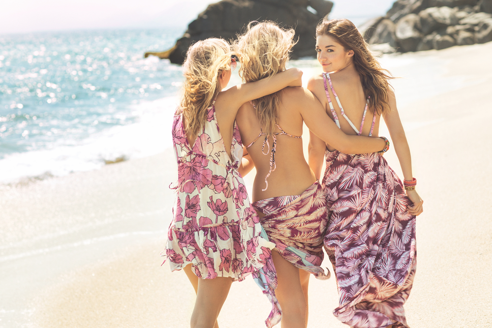 Friends walking on the beautiful beach wearing Maaji swimwear