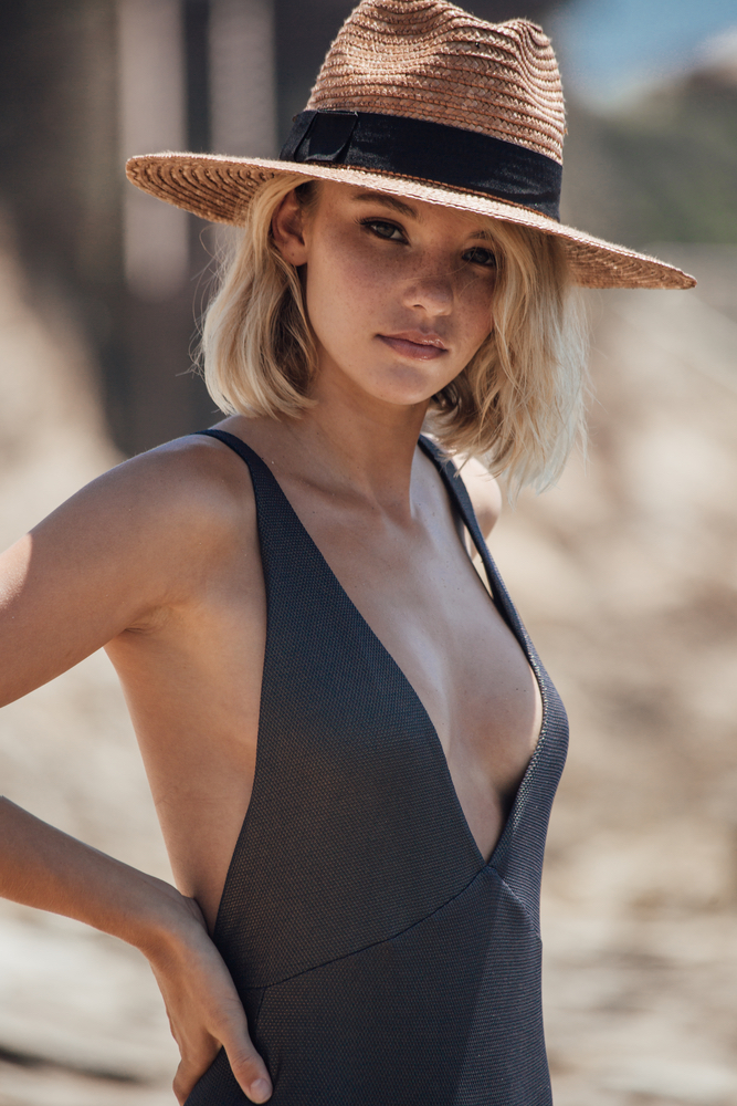 Blonde model in a beach hat and one piece bathing suit by TAVIK Swimwear Ophelia Swimwear
