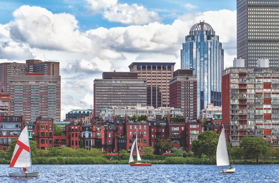 Sailboats cruising along the Charles River with a backdrop of the historic Back Bay neighborhood. VIE Magazine. The Sophisticate Issue