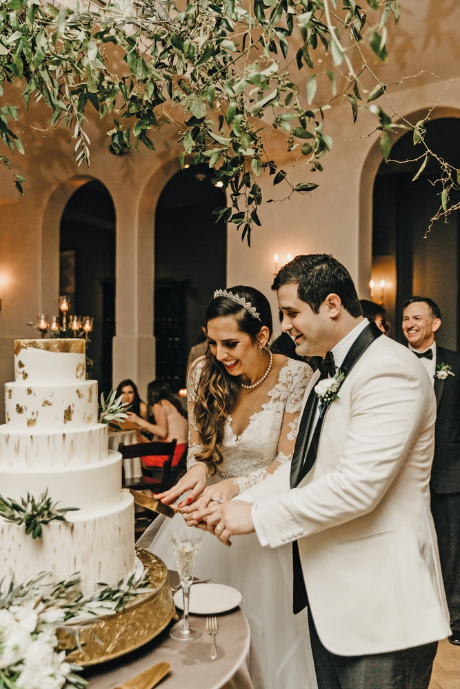 Sarah Elizabeth and Phillip cutting the cake at their Sicilian style New Orleans wedding The Sophisticate 2017