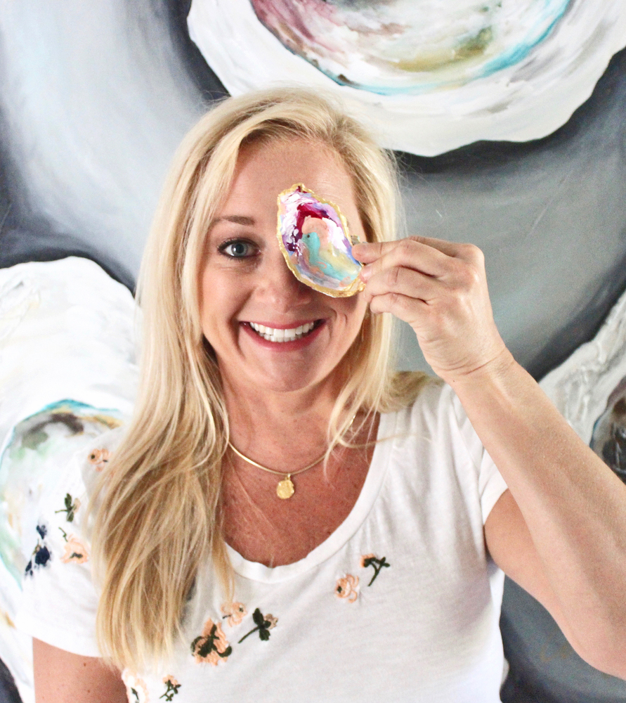 Artist Amy Fogg holding up a painted oyster