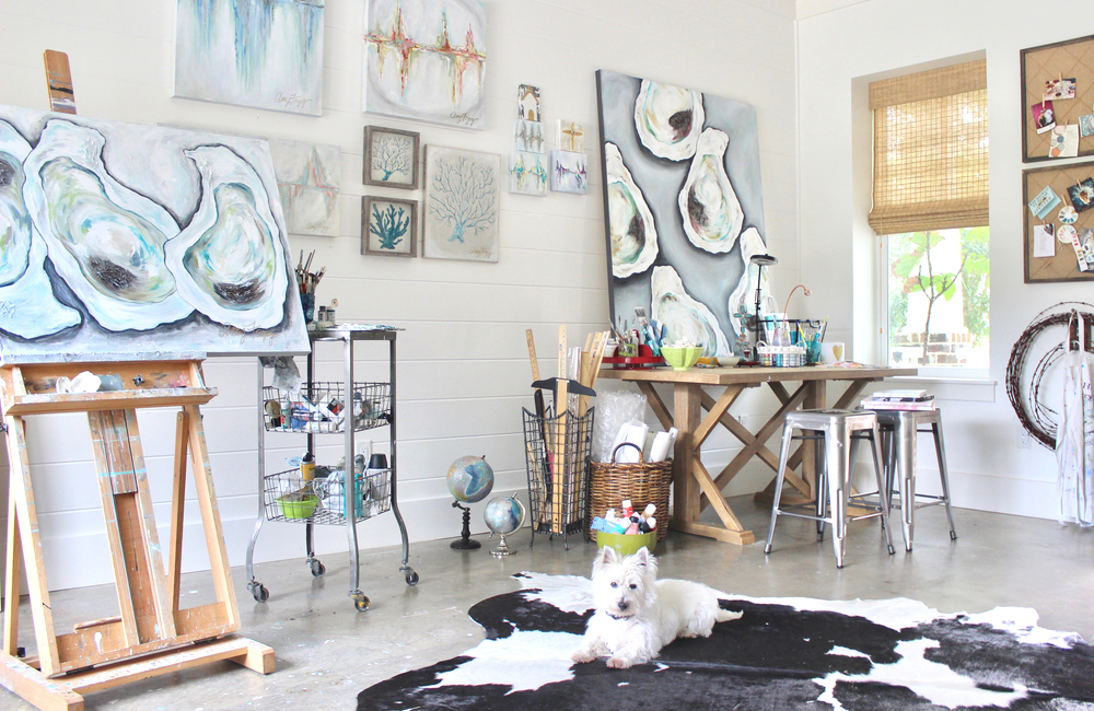 Amy Fogg's art studio with oyster paintings and her white dog