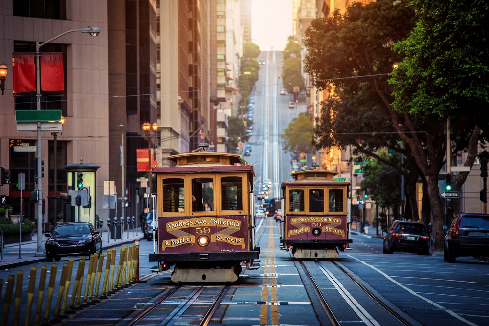Classic view of historic traditional Cable Cars riding on famous California Street in morning light at sunrise with retro vintage style cross processing filter effect, San Francisco, California