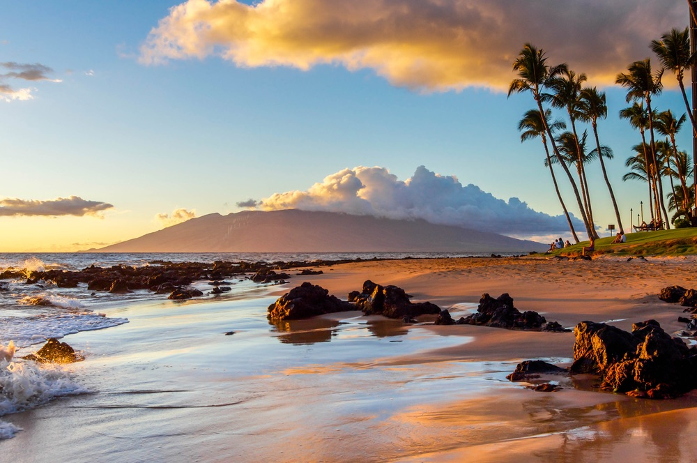 The sunset creates a warm glow on a beach in Maui, Hawaii