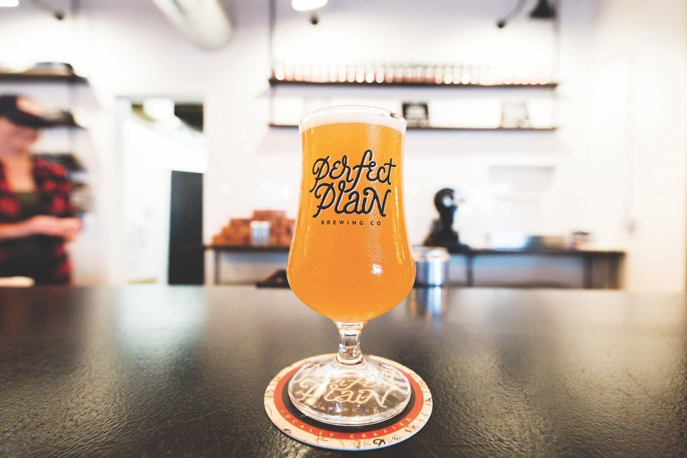 Shot of a beer from Perfect Plain Brewing Company, located in downtown Pensacola, Florida. The clear glass has their logo in black and is sitting on a black counter top at the bar