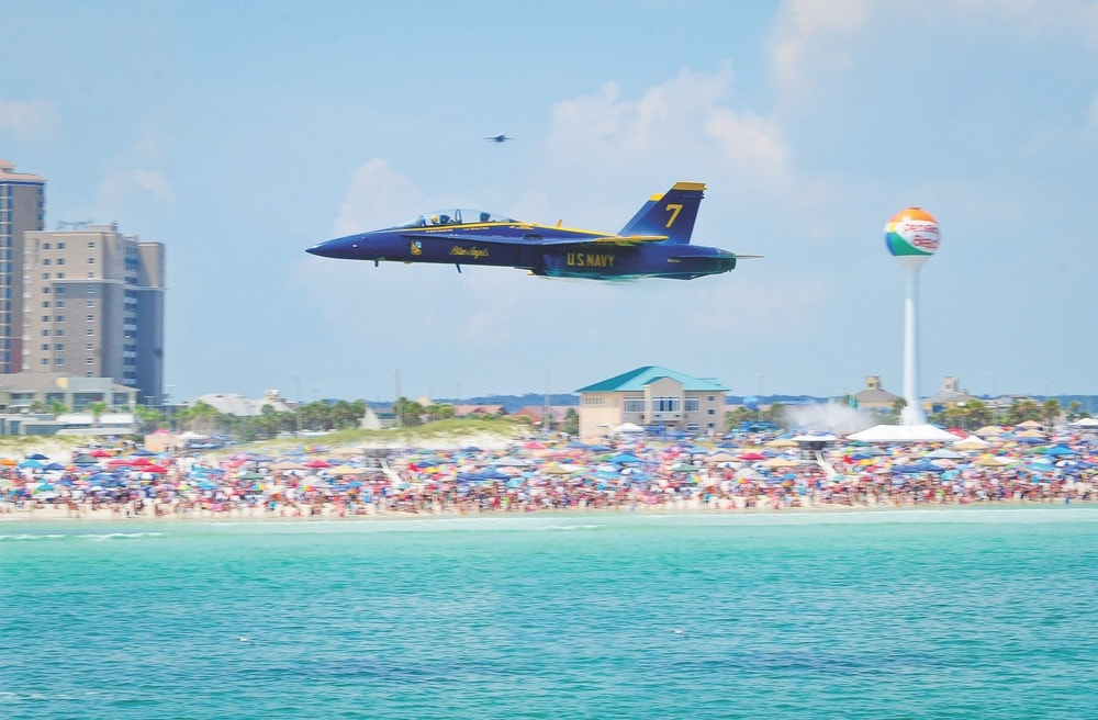 View of the Pensacola Beach during a Blue Angels show with a large crowd of people on the shoreline watching the plane fly by.