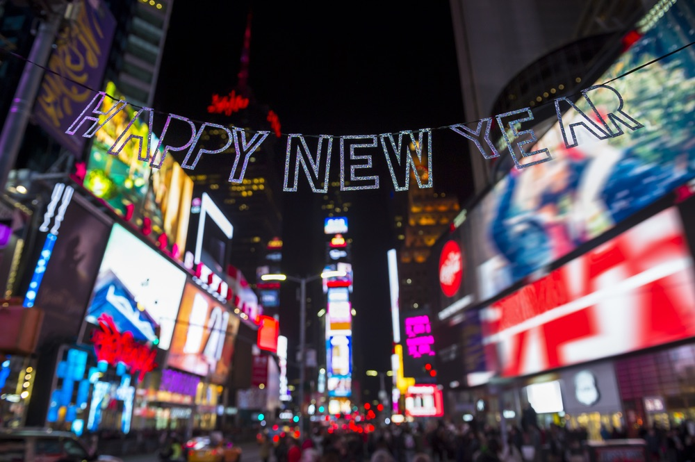 Glittery Happy New Year message strung across the flashing lights of Times Square, New York City