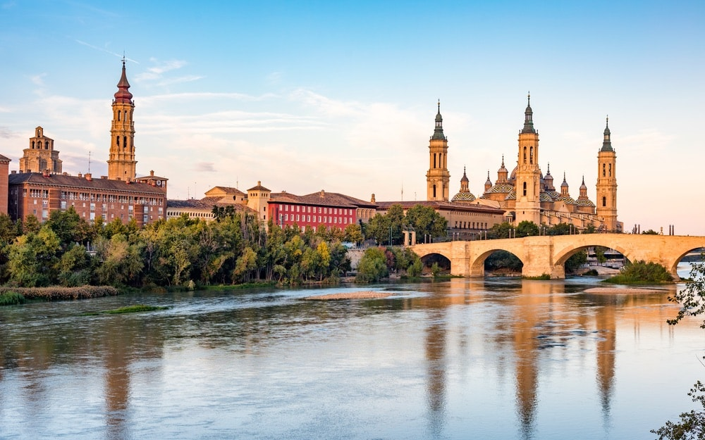 "The majestic Cathedral-Basilica of Our Lady of the Pillar in Zaragoza, along with the Puente de Piedra (meaning ""bridge of stone"")"