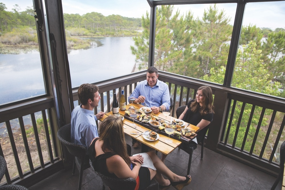 Two couples on a double date drinking wine and eating dinner in a screened in porch in a restaurant that's right on the lake in Walton County, Florida