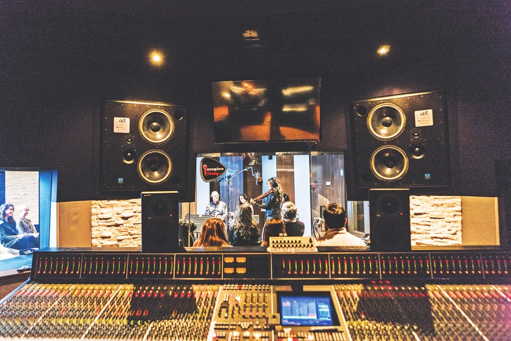 Natalie Stovall adds a fiddle overdub to the new track as Imagine attendees view the session from the control room at Sound Stage.