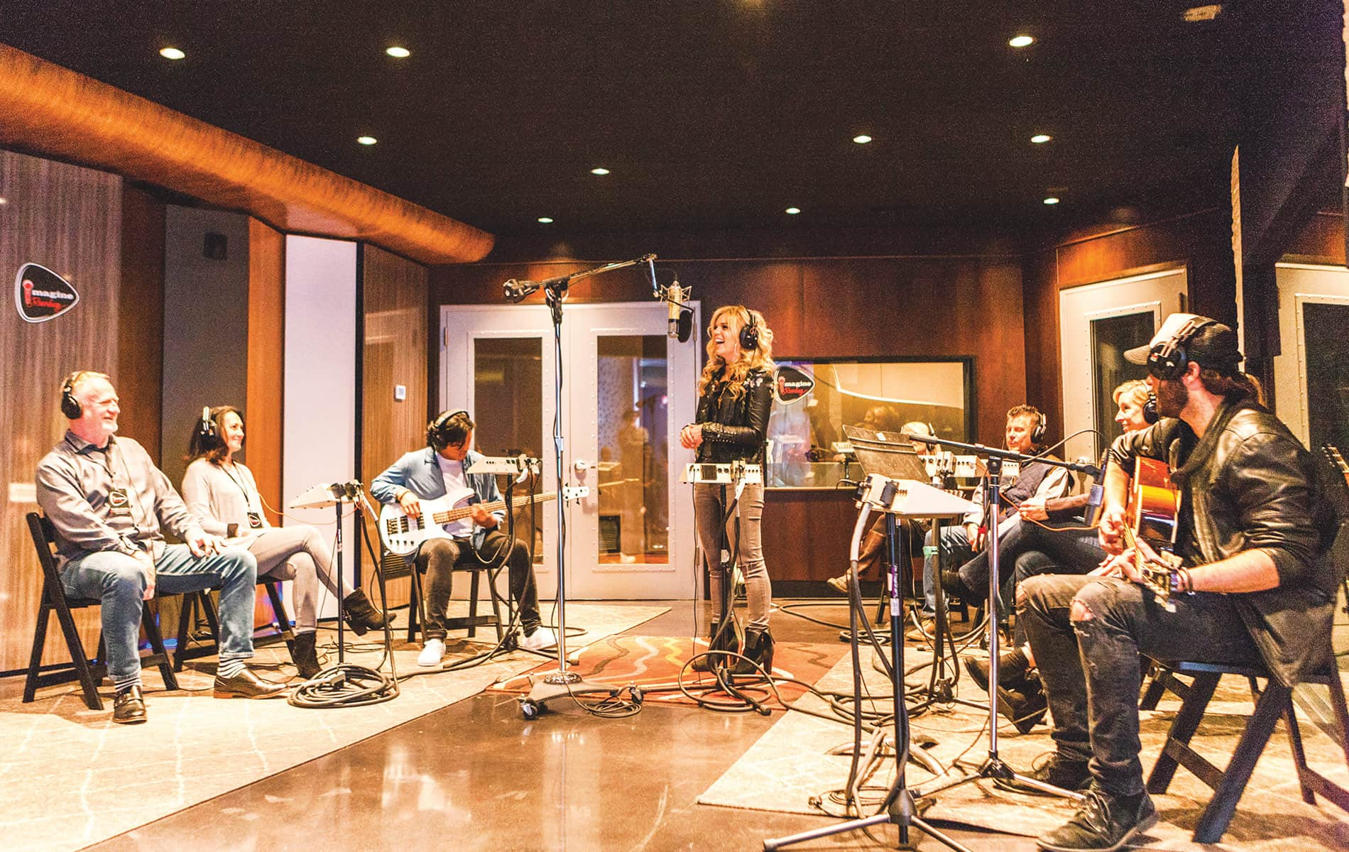 Recording artist Natalie Stovall sings a new song during a live Imagine Recordings session with studio musicians while attendees listen through headphones.