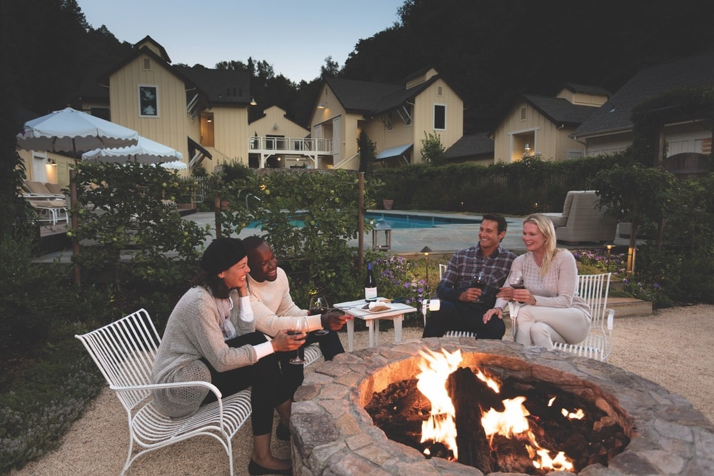 Sonoma County, California; Two couples enjoying the warm fire by the pool at Farmhouse Inn