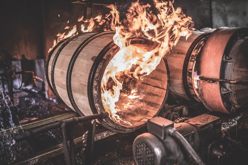 Barrels being fired to create a smoky-flavored bourbon