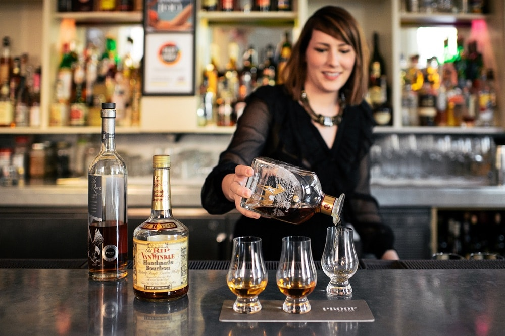 Mixologist at Proof on Main in pouring a flight of three bourbons for tasting; Louisville, Kentucky