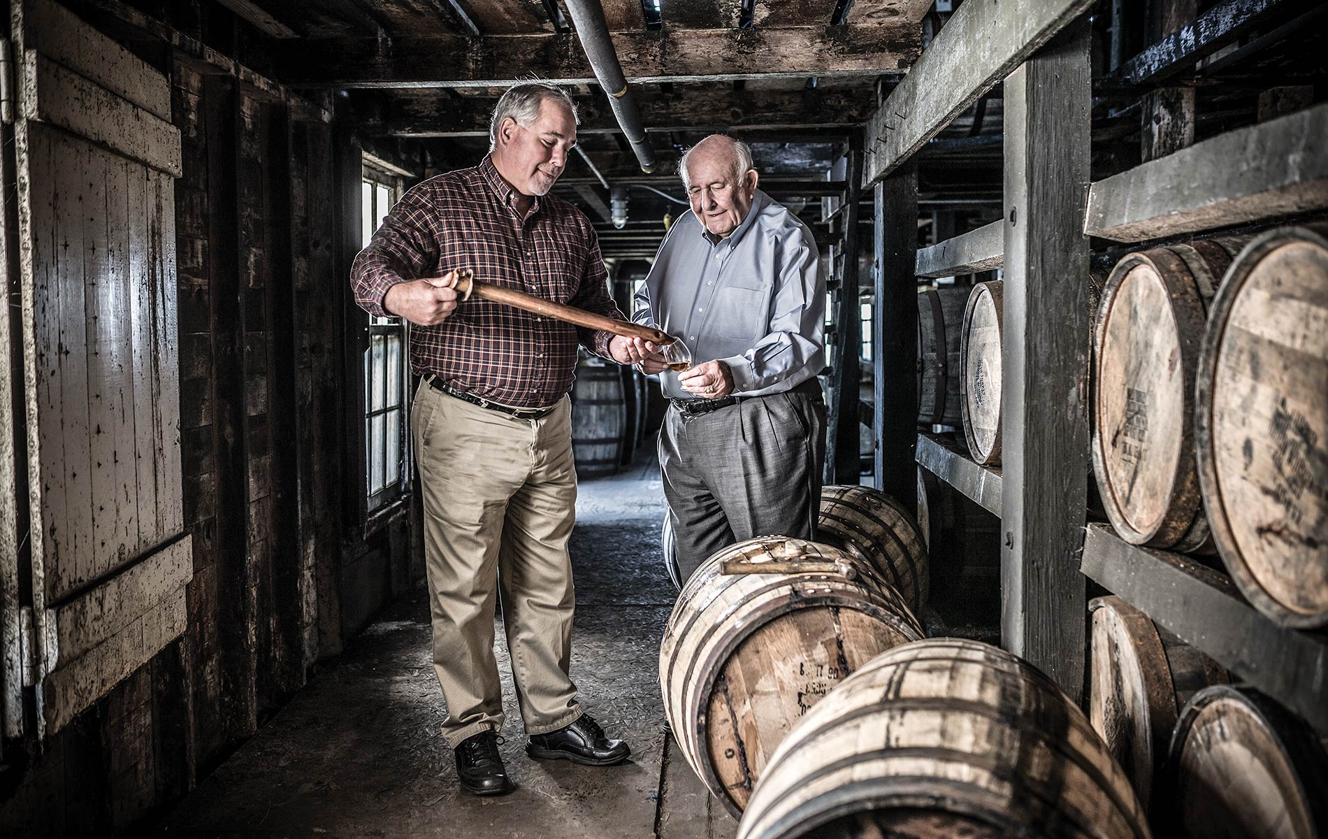 Master distiller at Wild Turkey Jimmy Russell (right) and his son, Eddie pulling a sample through a barrel