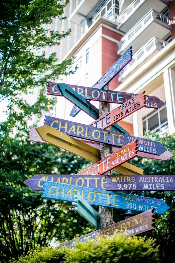 Directional sign with posts that each have a different location of Charlotte and the distance to get there