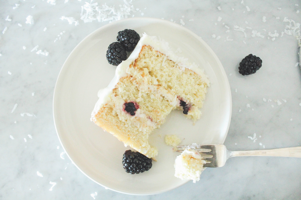 One slice of an eight-inch layer moist coconut cake with fresh blackberries and coconut cream cheese frosting on a white plate and topped with fresh blackberries