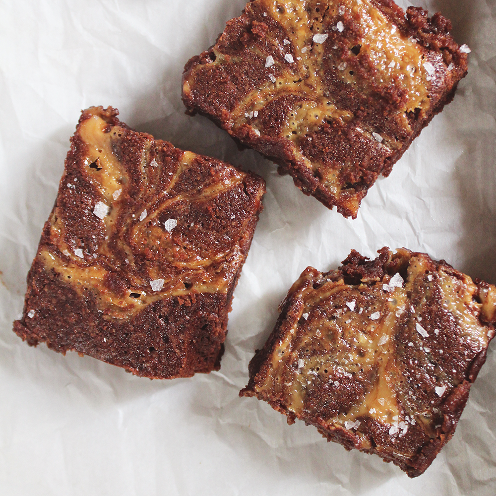 Three of Elisabeth's Salted Caramel Brownies cut into squares and sprinkled with sea salt