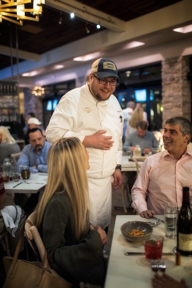 Chef at Emeril's Coastal Italian at Grand Boulevard in Miramar Beach, Florida talking with a couple at their table