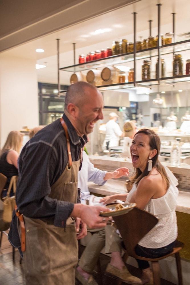 Customer and waiter having a great time at Emeril's Coastal Italian at Grand Boulevard in Miramar Beach, Florida