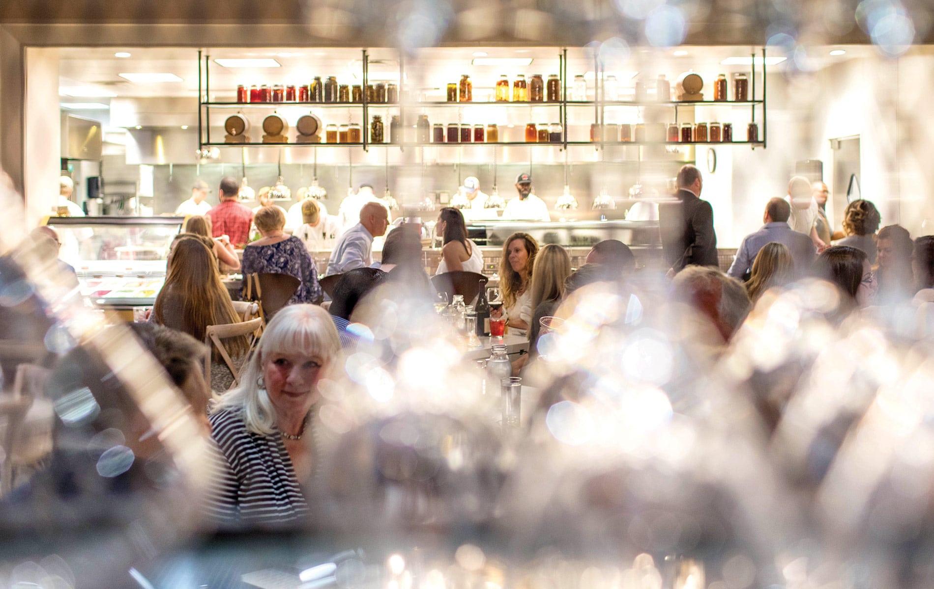 Looking through wine glasses at the dinning room area at Emeril's Coastal Italian at Grand Boulevard in Miramar Beach, Florida