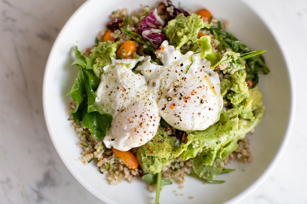 A healthy salad with avocado and a pouched egg.