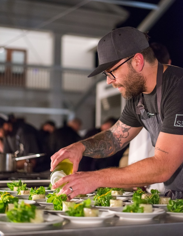 A chef preparing food at the Seeing Red Wine Festival.