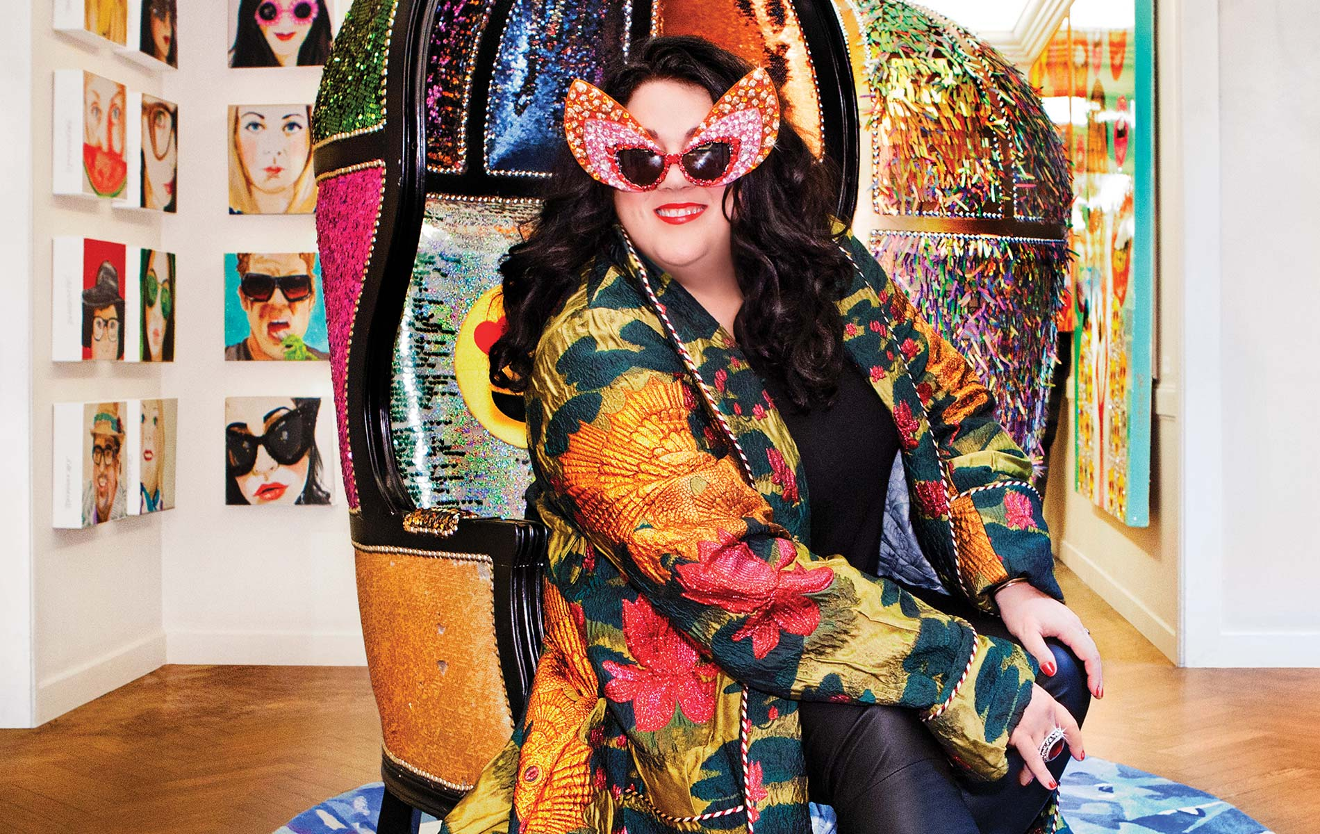 Ashley Longshore wearing a Gucci coat sitting in a customized Longshore chair on the seventh floor of Bergdorf Goodman during her pop-up gallery installment
