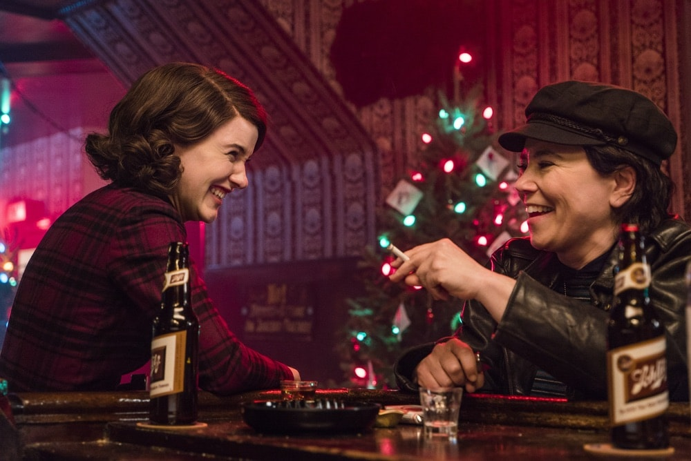 Rachel Brosnahan and Alex Borstein in Season 1 of The Marvelous Mrs. Maisel sharing a beer each at a bar at Christmas time.