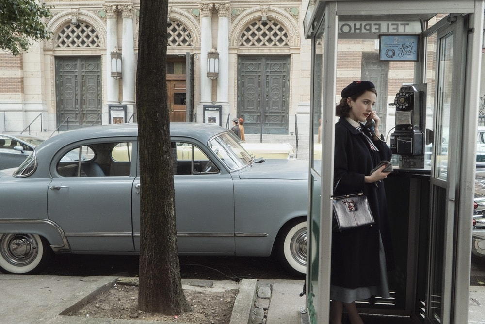 Midge Maisel talking on the phone in a phone booth