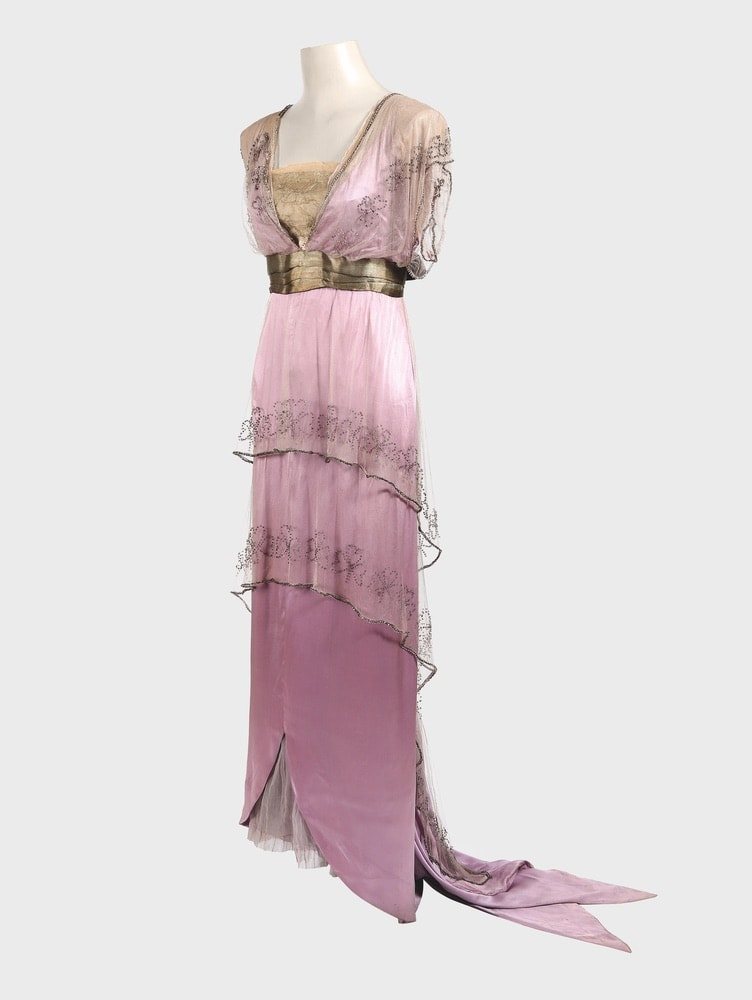 House of Worth formal dress made from two asymmetric tunics in chiffon, both longer at the back, with clover-leaf motifs embroidered in glass beads, covering a narrow silk satin underdress with a train of pointed streamers, gold lamé bodice, and belt.