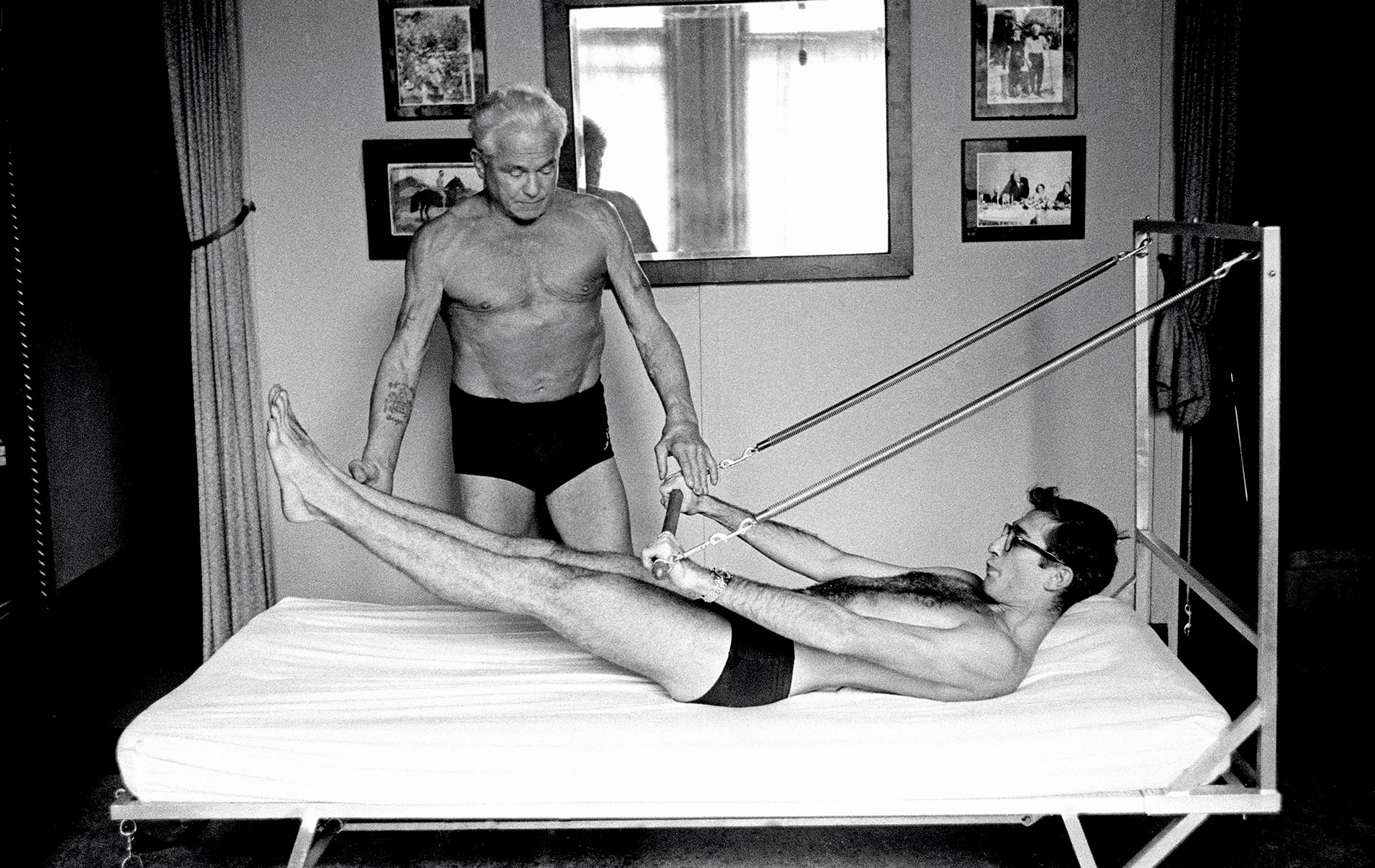 "Joseph Pilates offers photographer Chuck ""I.C."" Rapoport a firsthand demonstration of his Bednasium machine on October 4, 1961."